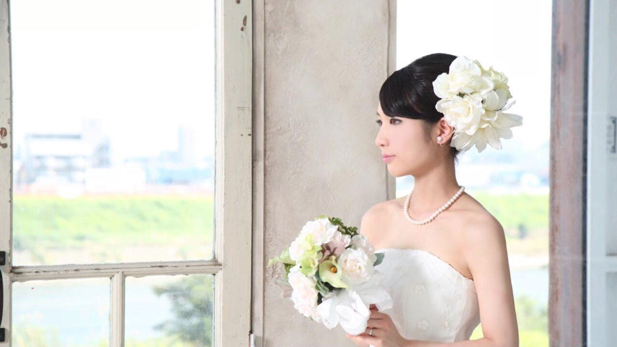 ブライダル ネックレスのパールをする花嫁。ウェディング ドレスに合わせたブーケとヘアード着用