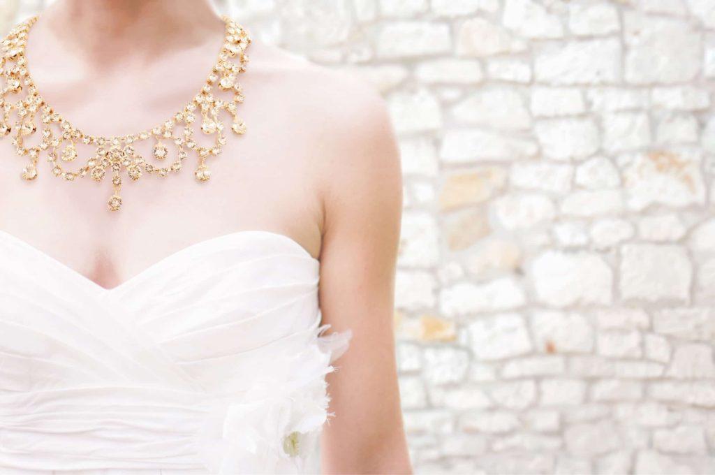 スワロフスキーを使ったブライダル ネックレスのゴールドを着用する花嫁。大ぶりで可愛らしいレースのデザイン No.81