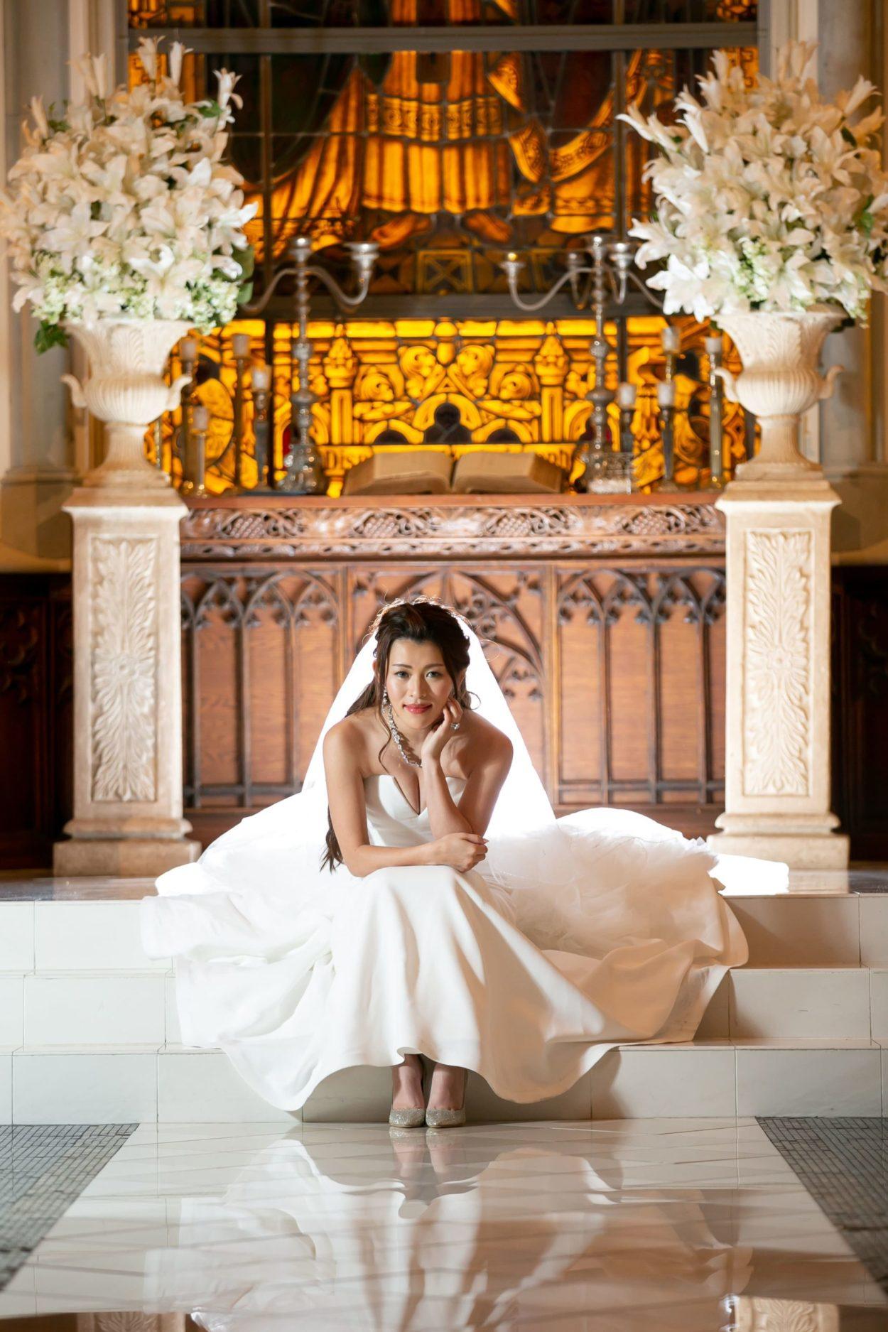 教会の前でウェディングドレスを着て微笑む花嫁