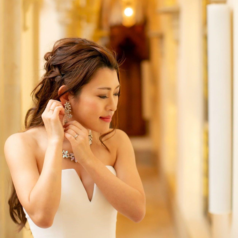 ブライダル イヤリングを試着する花嫁 ウェディングドレス着用